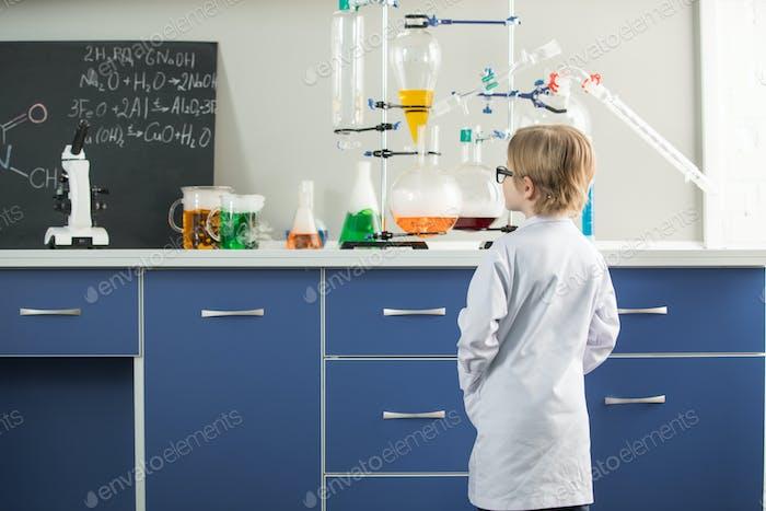 Rückansicht des kleinen Jungen tragen Labormantel im Wissenschaftslabor
