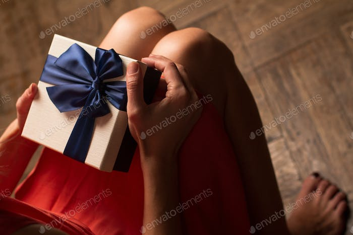 Woman holding a cardboard gift box with blue ribbon