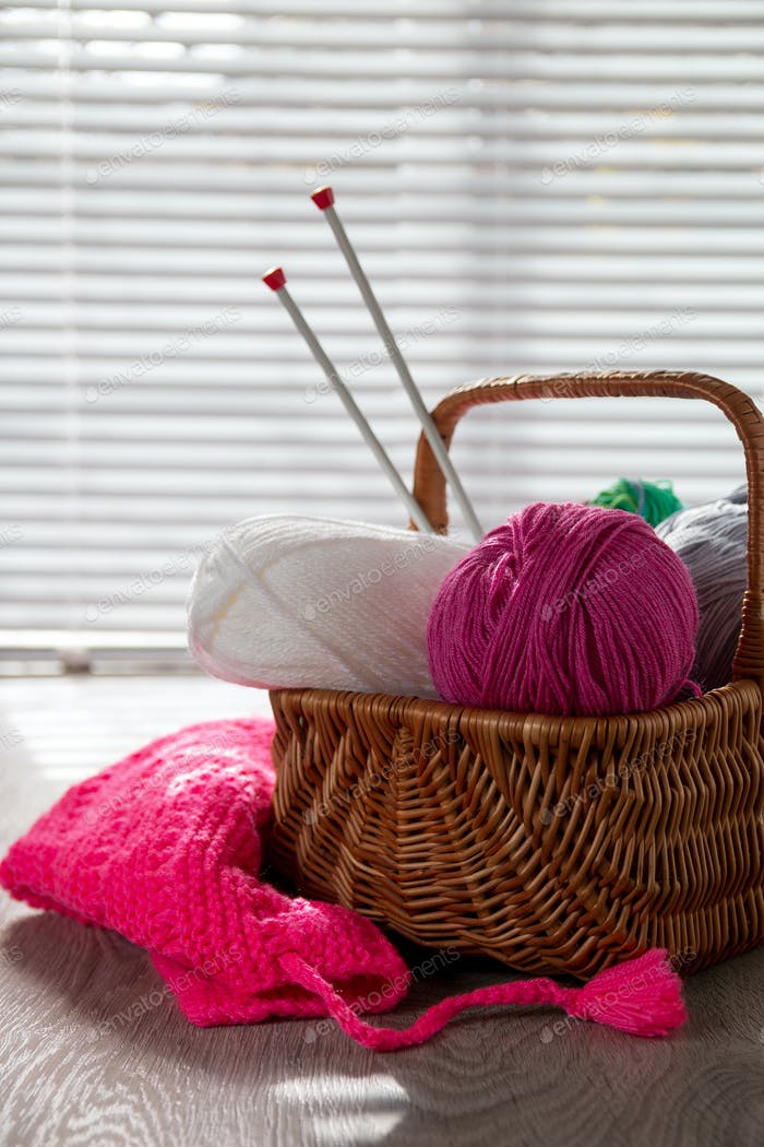 Ball of yarn and knitting needles in basket on a wooden grey table with window light. Handmade.