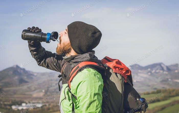 Wanderer auf einem Ausflug in die Natur - Tourist hat eine Pause während einer Trekkingtour.