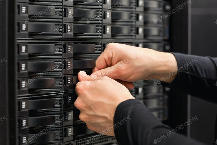 Male IT Engineer Adjusting Hard Drives In SAN At Datacenter