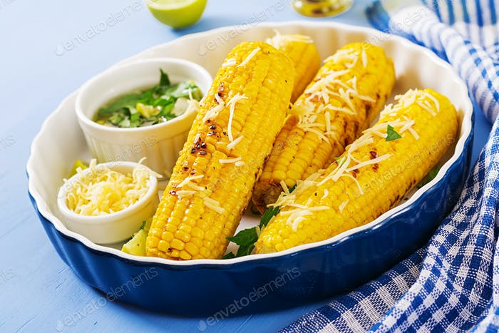 Delicious grilled  corn with basil-garlic sauce and lime. Tasty food.