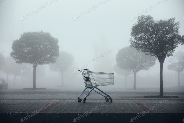 Abandoned shopping cart on parking lot in thick fog