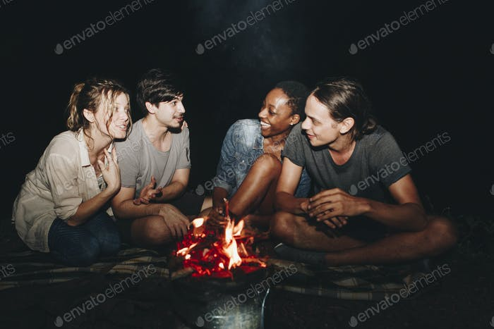Group of young adult friends sitting around the bonfire outdoors
