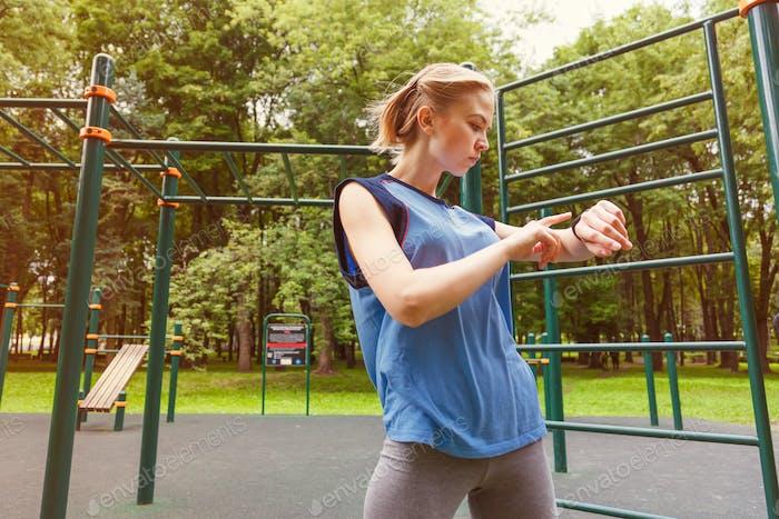 Frau mit Aktivitätstracker im Fitnessstudio