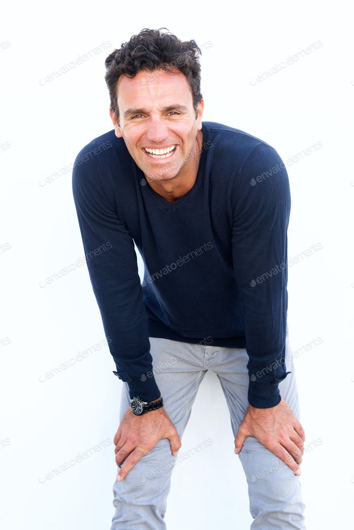 Handsome middle aged man laughing with hands on knees
