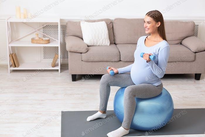 glücklich schwangere Dame trainieren mit Hanteln auf fitball