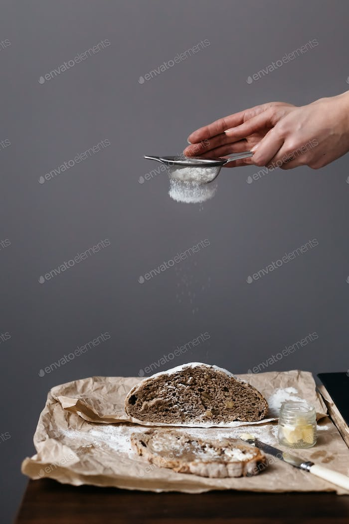 Woman sieving flour onto fresh loaf of bread