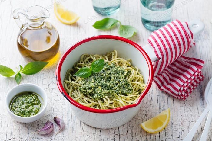 Pasta Spaghetti with Basil Pesto Sauce in Saucepan. White Wooden Background.