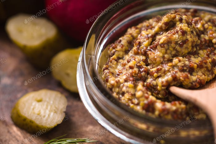 Mustard with seed in the glass bowl on the kitchen table horizontal