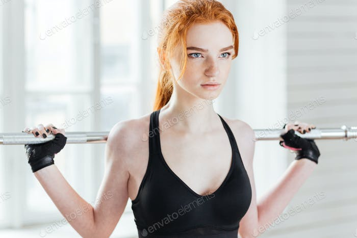 Close-up portrait of a woman doing exercises with barbell