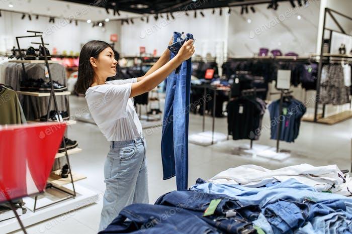 Fröhliche Frau Wahl Jeans im Bekleidungsgeschäft