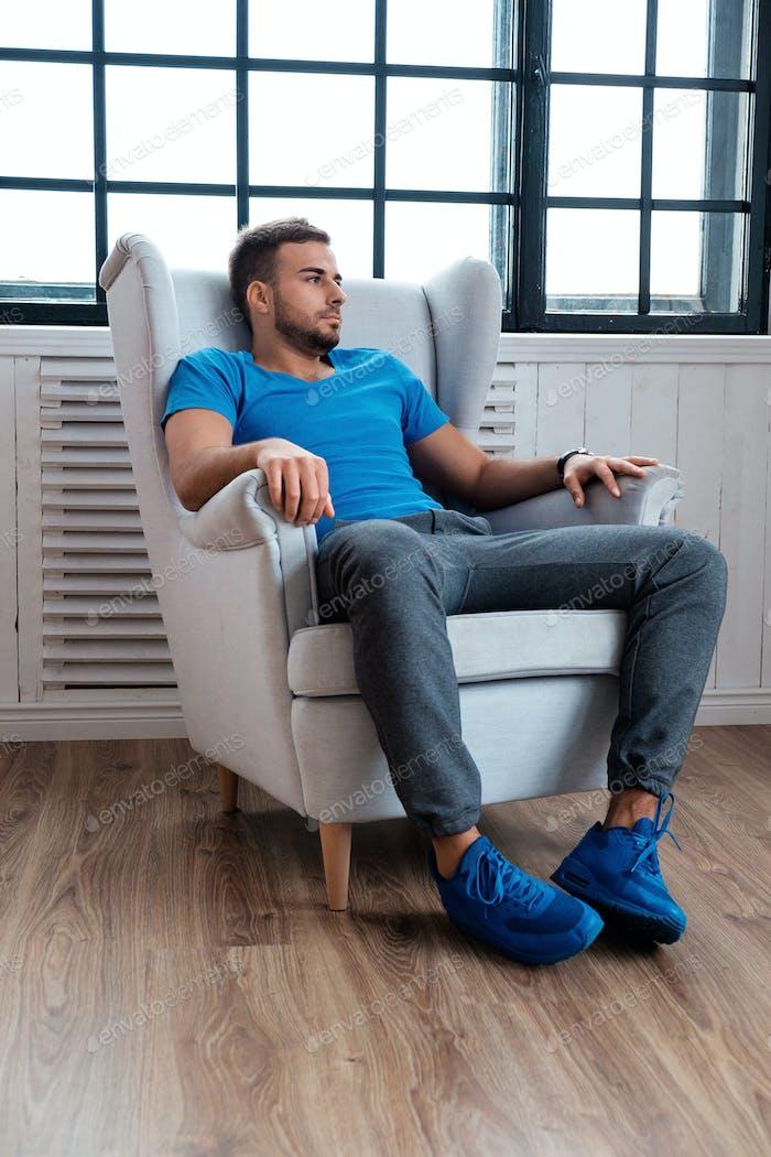 Бородатый мужчина в кресле.