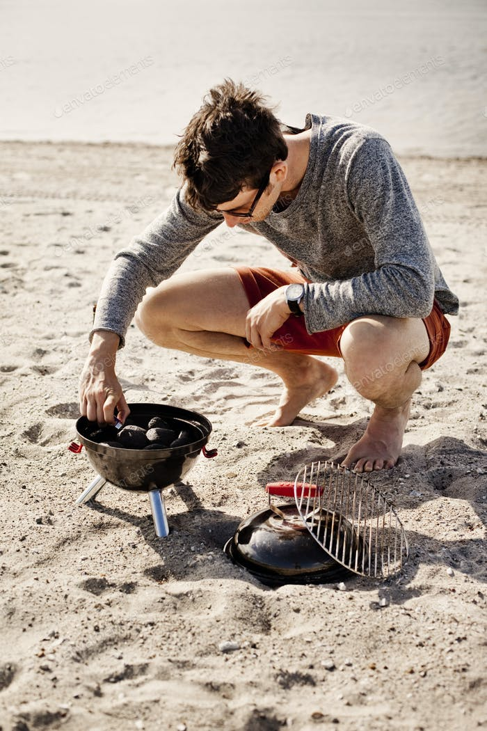 Full length of young man lighting barbeque on sandy beach