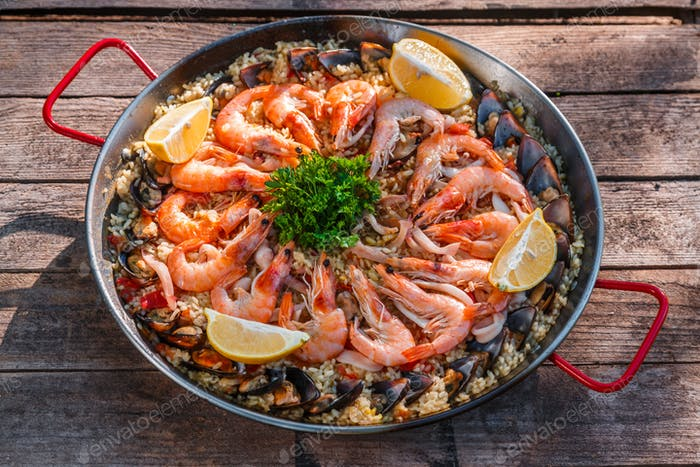 Traditional seafood paella in the fry pan on a wooden old table, top view