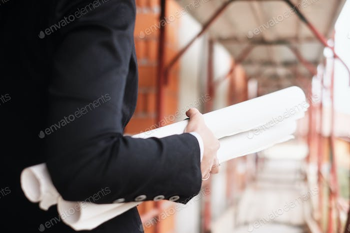 Woman Working As Engineer Holding Building Plans