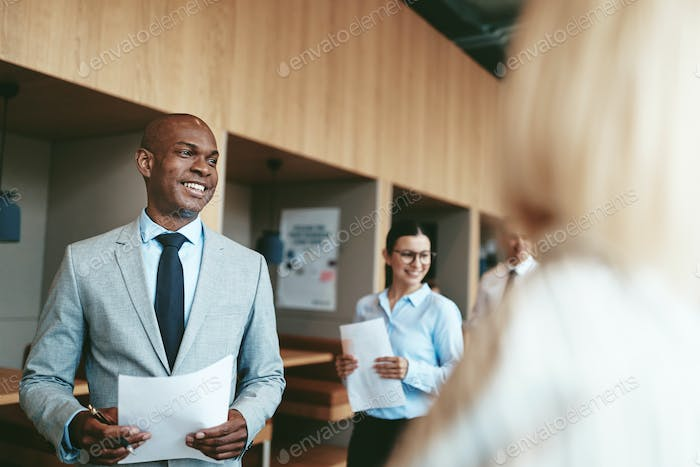 Smiling African American businessman walking with colleagues in an office