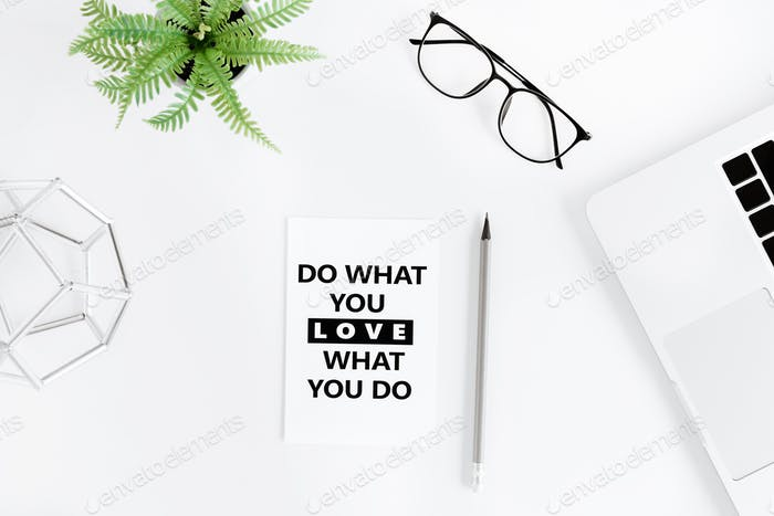 flat lay with Do what you love and love what you do motivational quote on modern workplace with