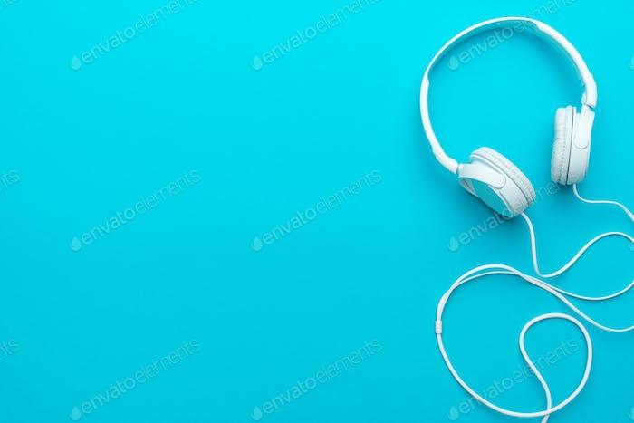Minimales Foto von weißen Kopfhörern mit Kabel auf blauem Hintergrund mit Kopierraum.