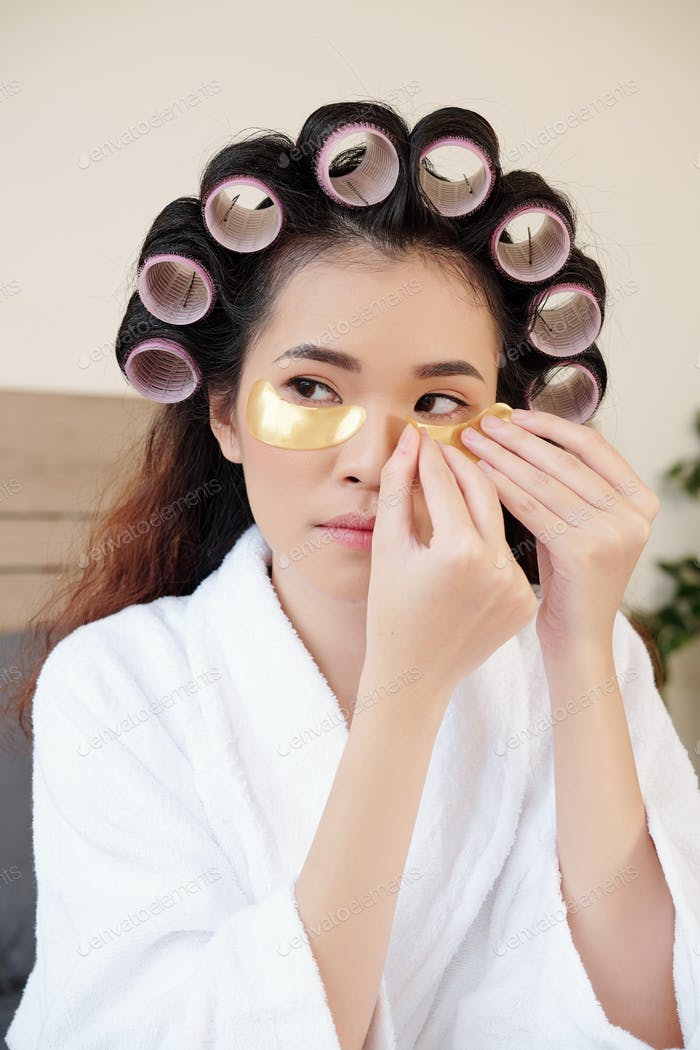 Woman applying undereye patches