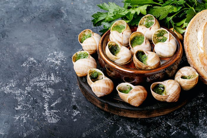 Baked snails with garlic butter and fresh herbs in a frying pan, selective focus