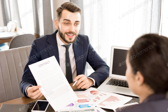 Confident businessman showing contract to colleague