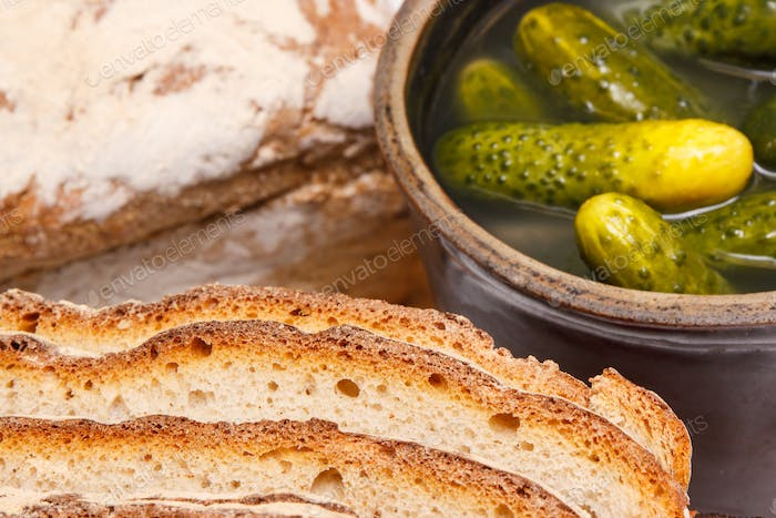 Slices of fresh baked loaf of rye or wheat bread and pickled cucumbers in clay pot