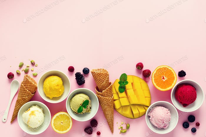 Ice cream balls in bowls, waffle cones, berries, orange, mango, pistachio on pink shabby chic