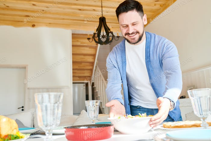 Happy Mature Man Setting Table