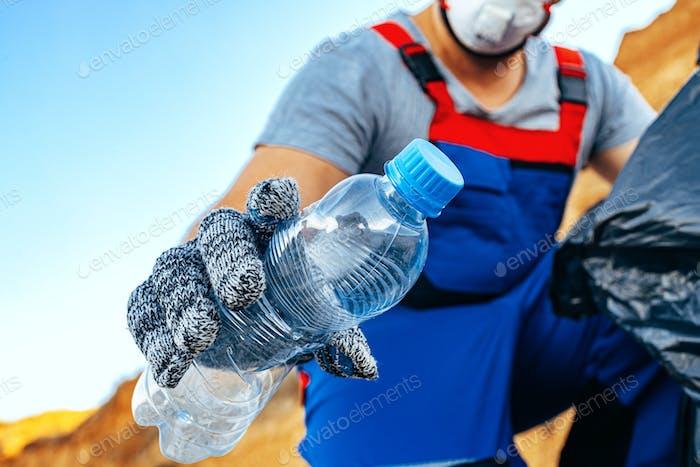 Hand eines ehrenamtlichen Mannes packt Plastikmüll in einen Müllsack und säubert den Strand