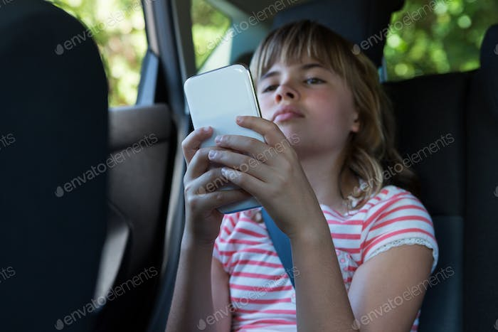 Teenage girl using mobile phone in the back seat of car
