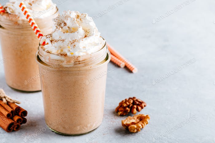 Pumpkin and carrot spice latte with whipped cream and cinnamon in glass jars