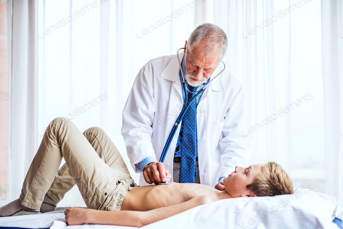 Senior doctor examining a small boy in his office.
