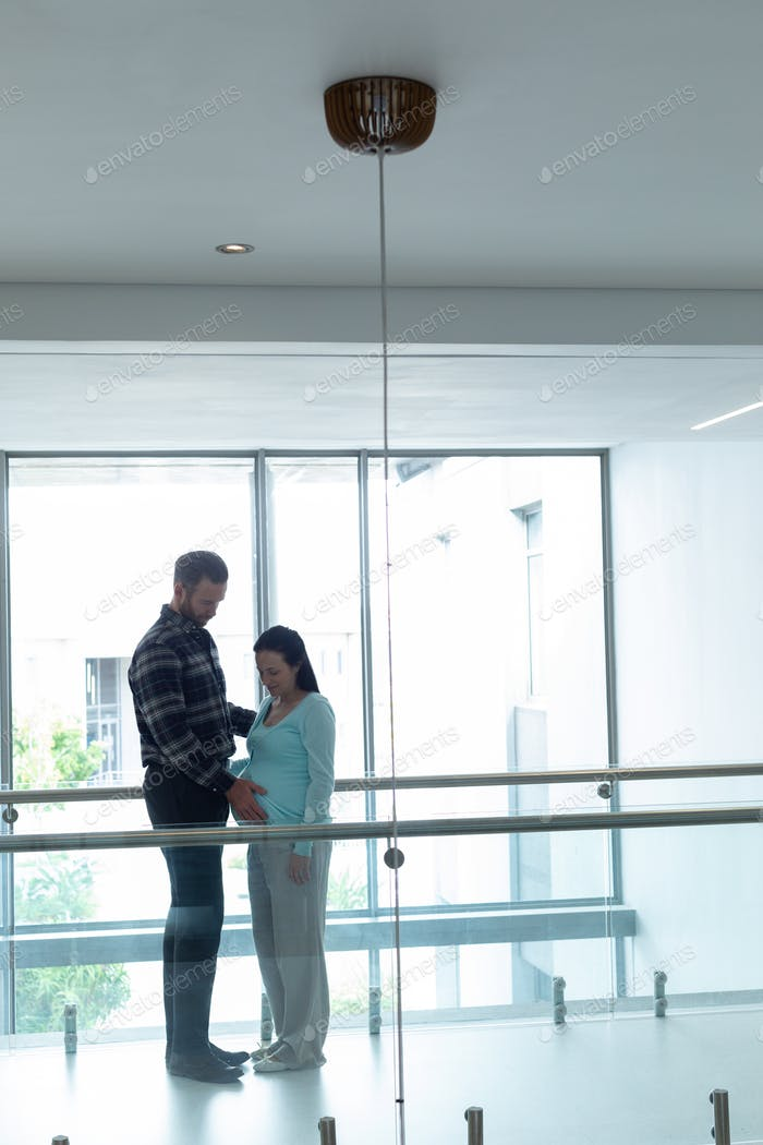 Side view of Caucasian man comforting pregnant woman in the corridor at hospital