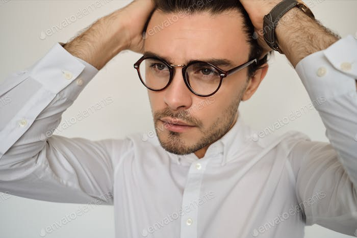 Portrait of young handsome man in white shirt and eyeglasses thoughtfully looking aside