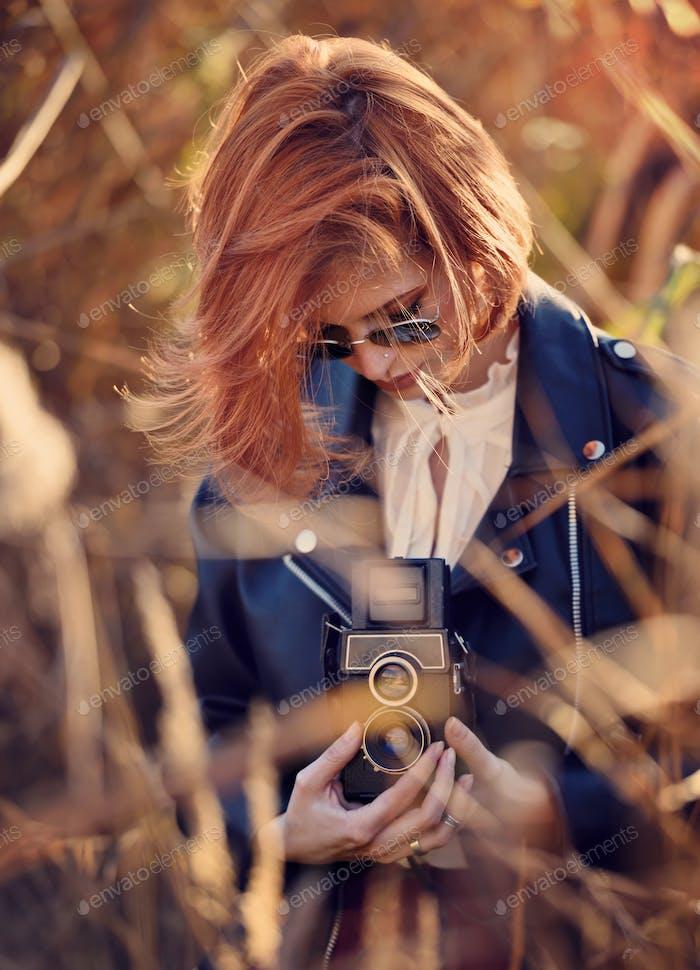 Schöne junge rothaarige Frau schießt auf einer Retro-Kamera