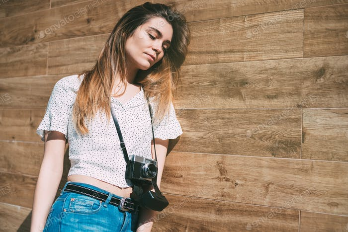 Beautiful woman with vintage old camera standing at a wood wall