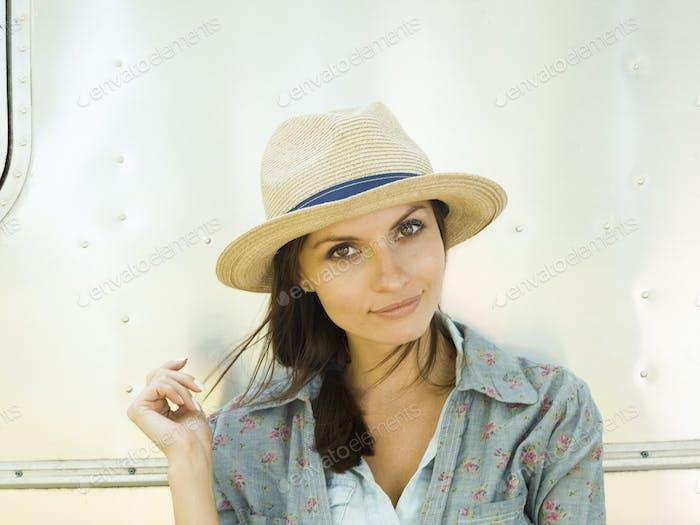 Eine junge Frau in einem Strohhut, ihr Kopf geneigt sah neugierig.