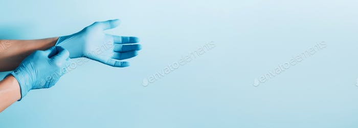 Woman doctor wears medical gloves over blue background. Copy space. National Doctors' Day