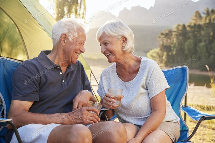 Senior Couple Enjoying Camping Vacation By Lake Making A Toast