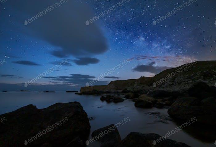 Night sky over rocky coastline