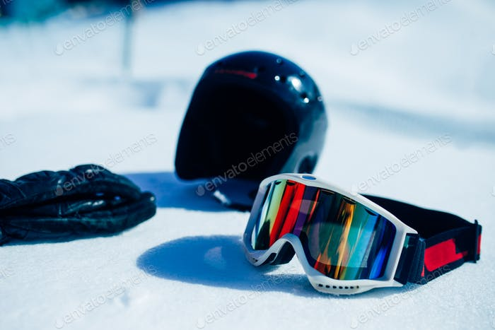 Helmet, glasses and gloves on the snow closeup