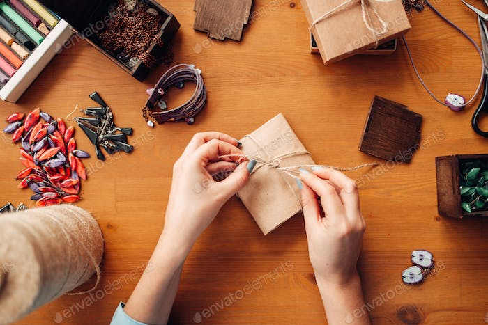 Female person tie a bow on a gift box, needlework