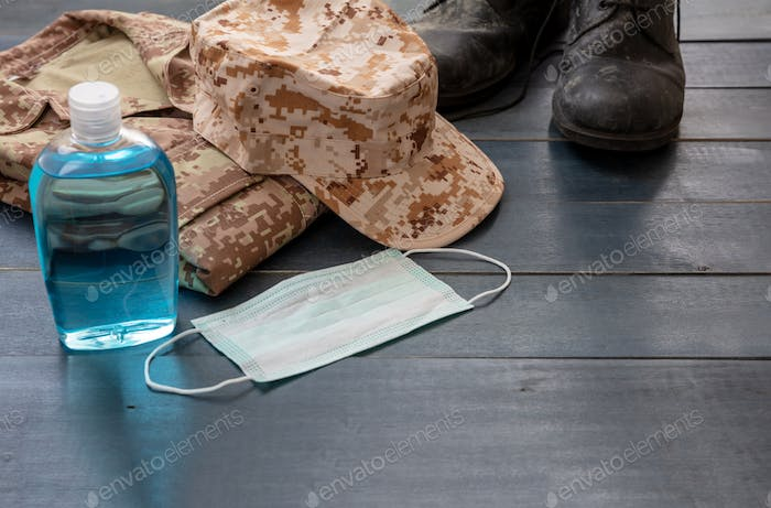 Army coronavirus protection concept. Hand sanitizer and US army gear on blue background.