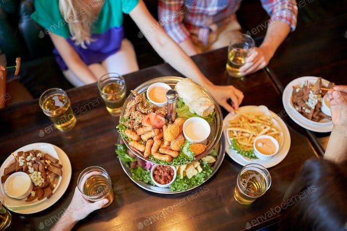 друзья едят и пьют в баре или пабе