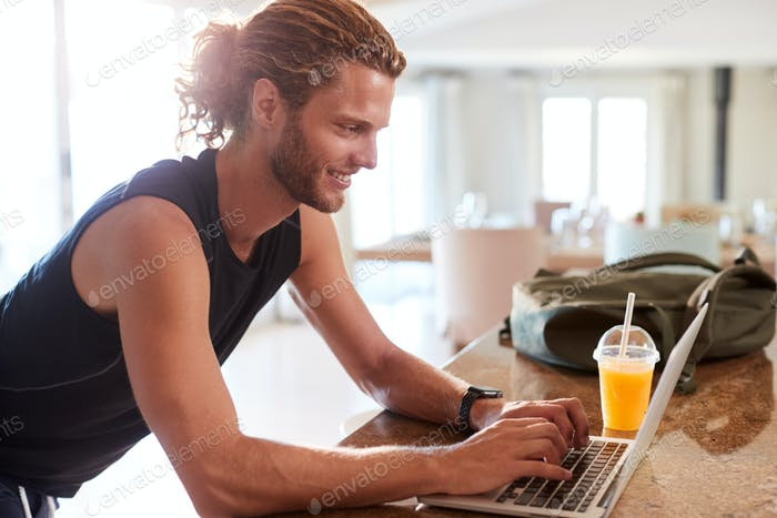Millennial white man checking fitness app on laptop at home after a workout, side view