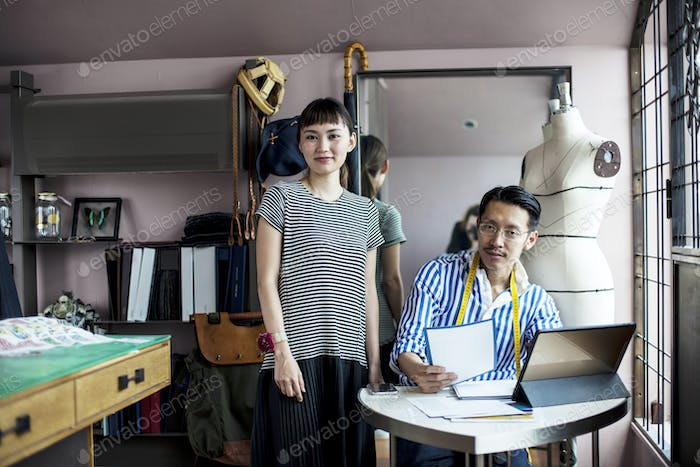 Japanese male and female fashion designers working in a studio.