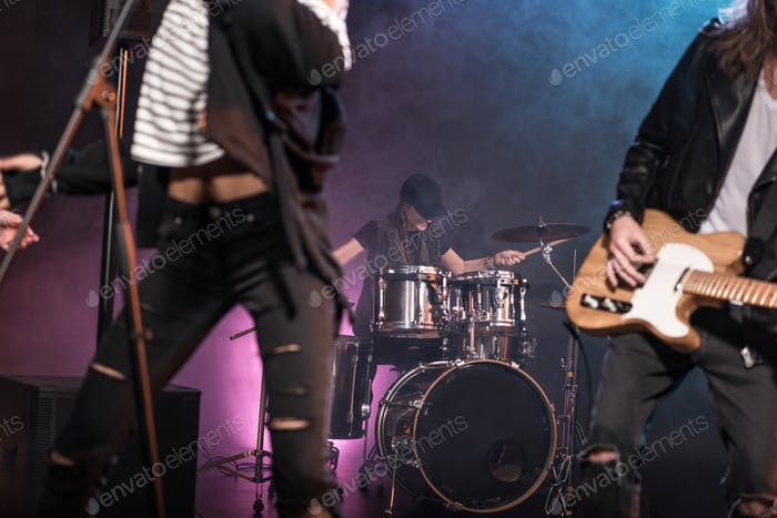 Young rock and roll band performing hard rock music on stage