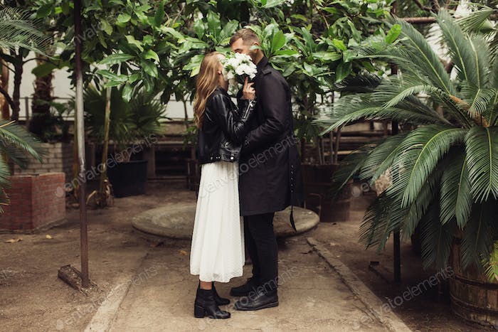 Young beautiful couple covering faces with little bouquet of whi
