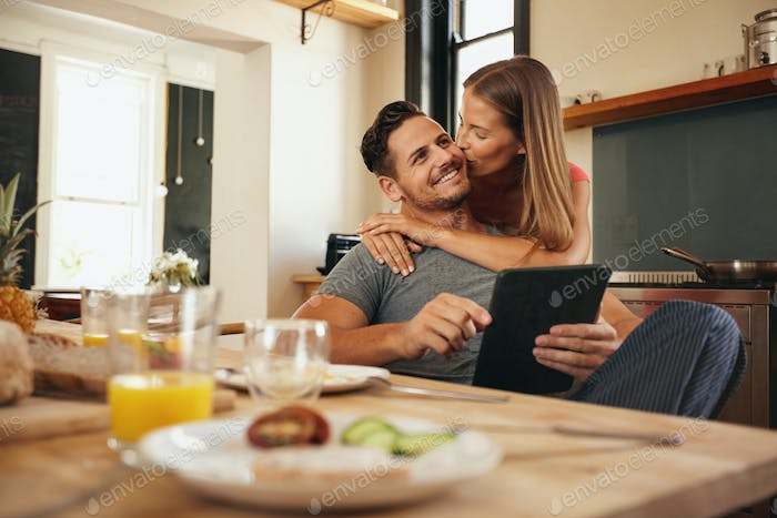Woman giving good morning kiss to her boyfriend in kitchen